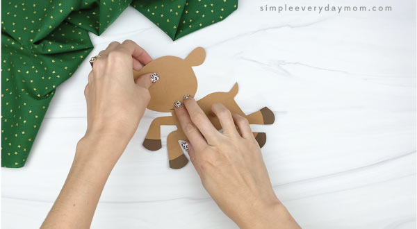 hands gluing head to paper rudolph craft