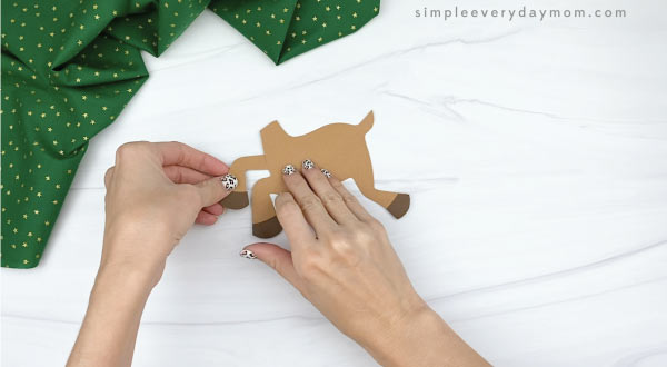 hands gluing legs to paper rudolph craft