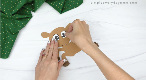 hands gluing eyes to paper rudolph craft