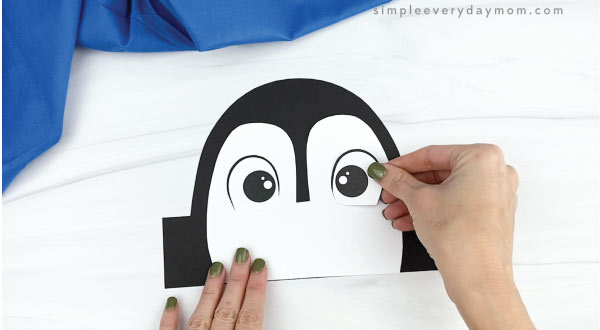 hands gluing eyes onto penguin headband craft