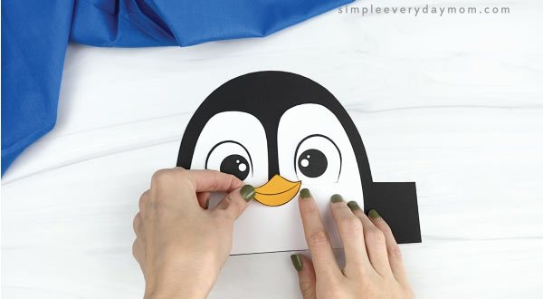 hands gluing beak onto penguin headband craft