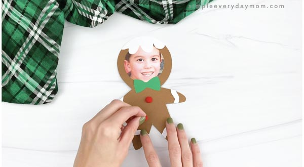 hand gluing pom pom buttons to gingerbread man craft