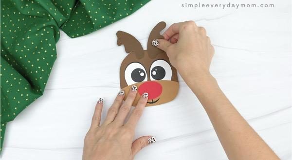 hand gluing antlers to reindeer Christmas card