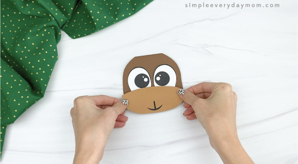 hand gluing mouth to reindeer Christmas card
