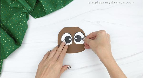 hand gluing eyes to reindeer Christmas card