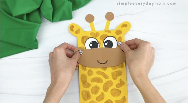 hands gluing horns to paper bag giraffe craft