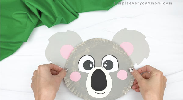 hand gluing ears to paper plate koala craft