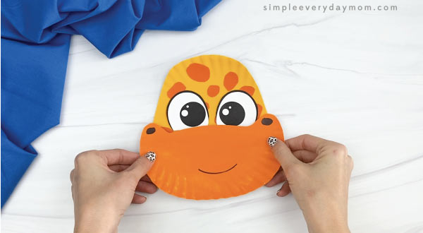 hands gluing mouth to paper plate giraffe