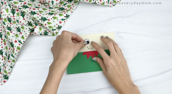 hands gluing eyes to elf toilet paper roll craft