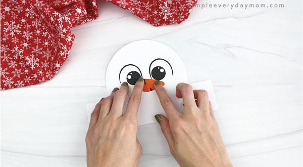 hands gluing nose to snowman headband craft