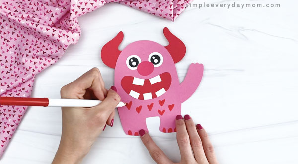 hand drawing hearts onto valentine love monster craft
