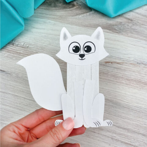 hand holding popsicle stick arctic fox craft