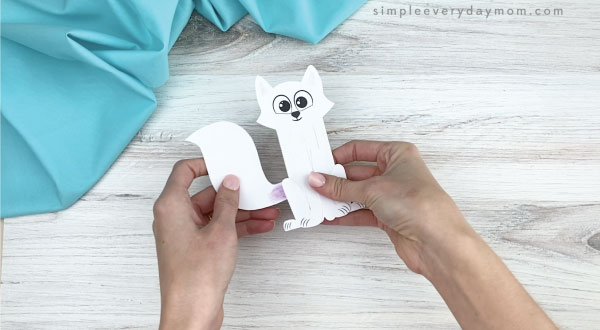 hands gluing tail to popsicle stick arctic fox
