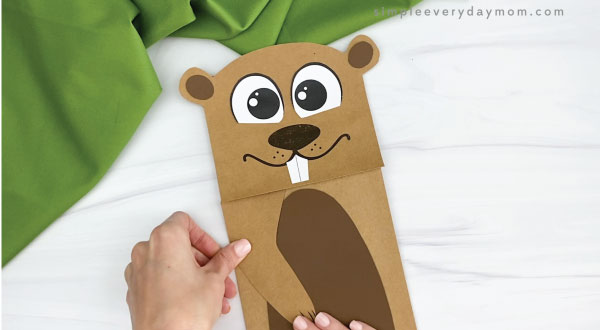 hands gluing arms to paper bag groundhog craft