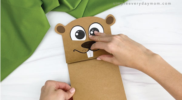 hands gluing body to paper bag groundhog craft