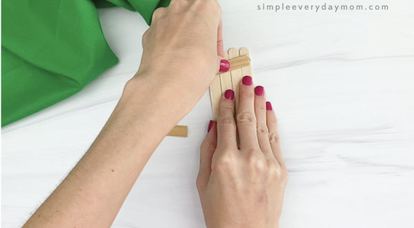 hand gluing popsicle sticks together