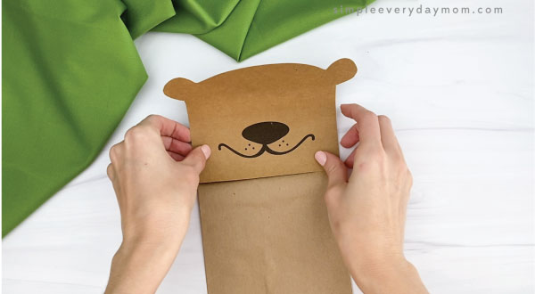 hands gluing head to paper bag groundhog craft
