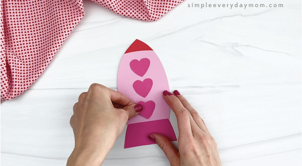 hands gluing hearts to rocket valentine craft
