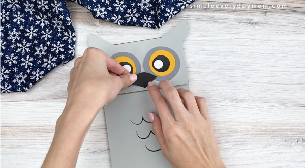 hands gluing beak to paper bag owl craft