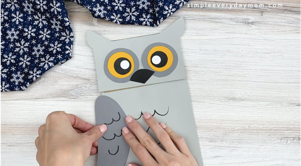 hands gluing wings to paper bag owl craft