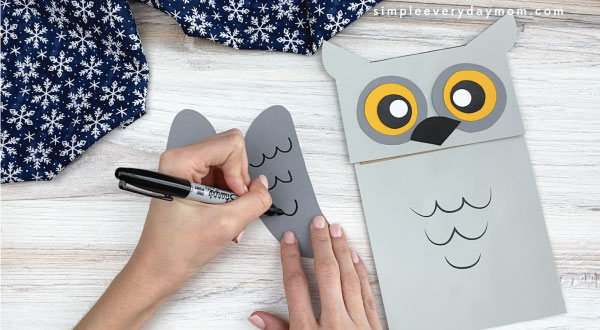 hands drawing feathers on paper bag owl craft wings