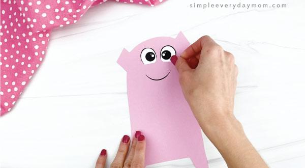 hand gluing eye to pig valentine craft