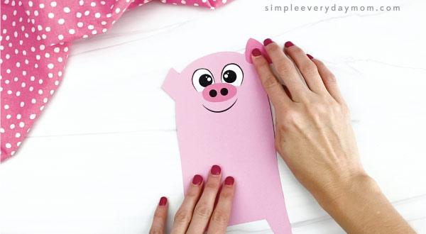 hand gluing ear to pig valentine craft