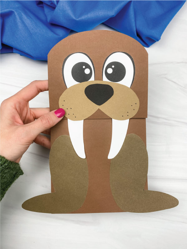 hand holding walrus paper bag craft