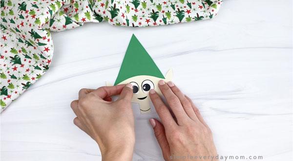 hands gluing eyes onto paper elf craft