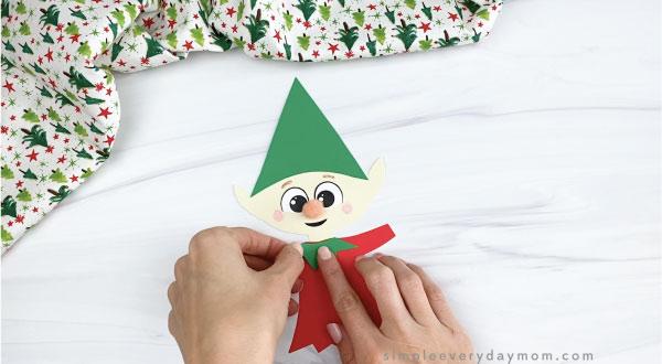 hands gluing shirt trim to paper elf craft