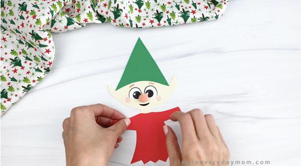 hands gluing shirt to paper elf craft