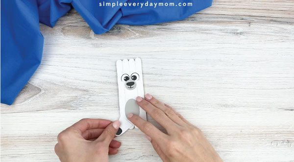 hands gluing outer legs onto popsicle stick polar bear craft