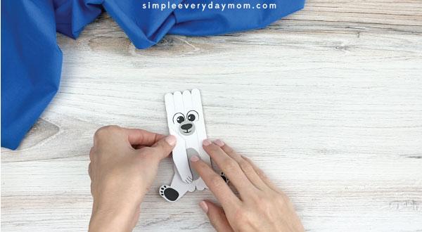 hands gluing inner legs onto popsicle stick polar bear craft