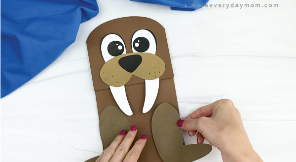 hand gluing flippers to paper bag walrus craft