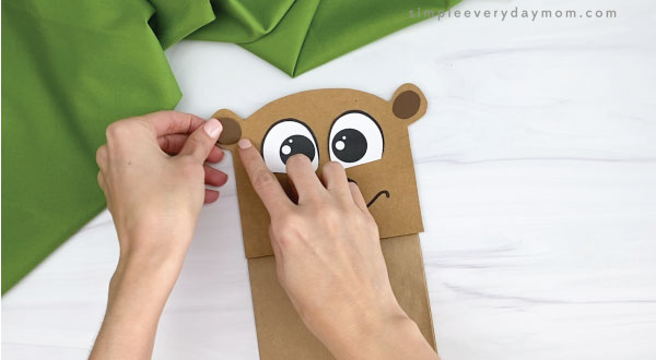 hands gluing inner ears to paper bag groundhog craft