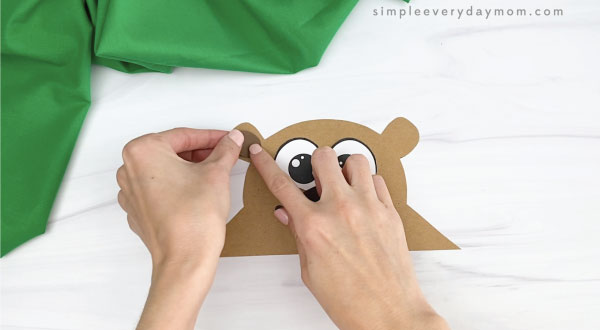 hands gluing inner ears onto groundhog headband craft