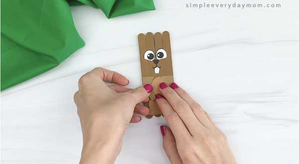 hand gluing arms onto popsicle stick groundhog craft