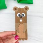 hand holding popsicle stick groundhog craft