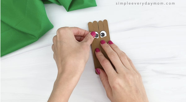 hand gluing eyes to popsicle stick groundhog craft