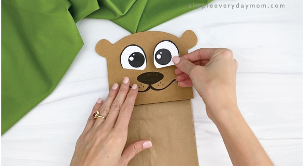 hands gluing eyes to paper bag groundhog craft