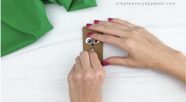 hand gluing teeth onto popsicle stick groundhog craft