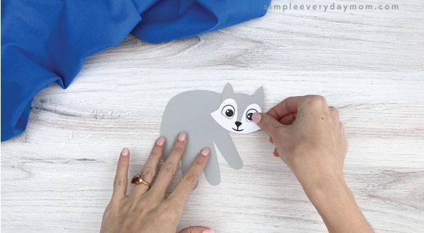 hand gluing head to handprint arctic fox craft