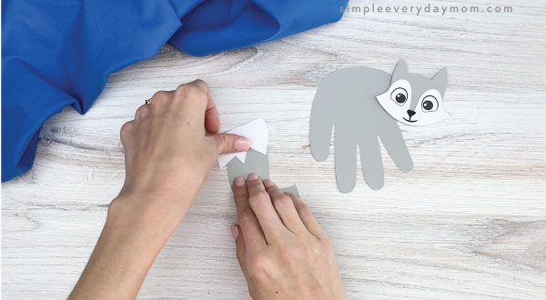 hand gluing tail tip to handprint arctic fox craft