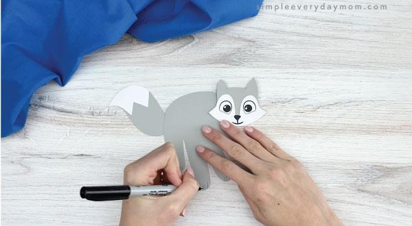 hand drawing paws onto handprint arctic fox
