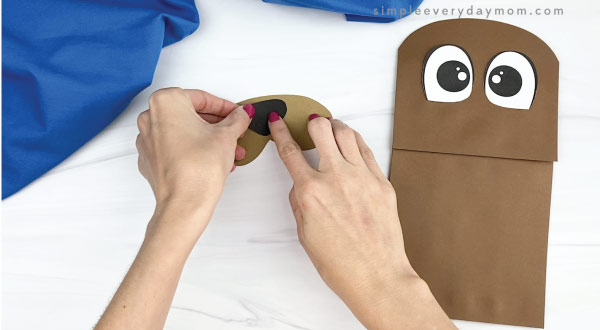 hand gluing nose to paper bag walrus mouth