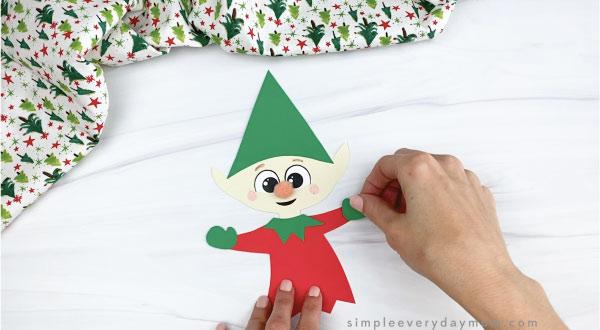 hands gluing mitten onto paper elf craft