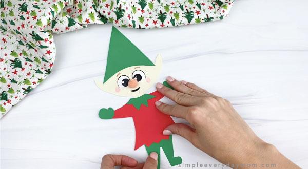 hands gluing pants onto paper elf craft