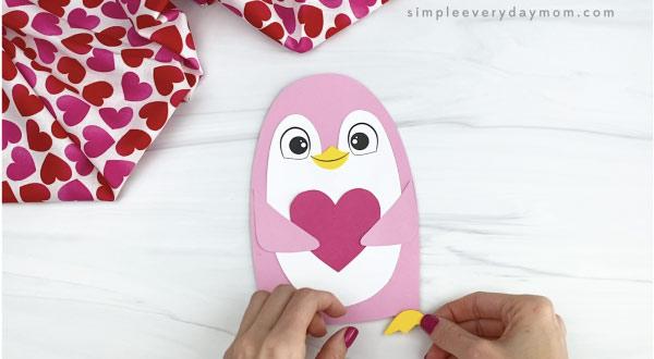 hand gluing feet onto penguin valentine craft