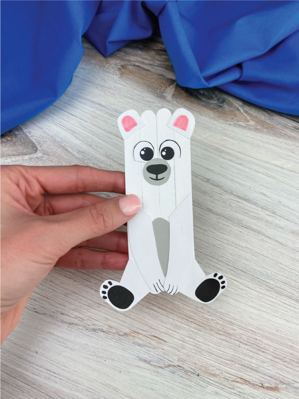 hand holding popsicle stick polar bear craft