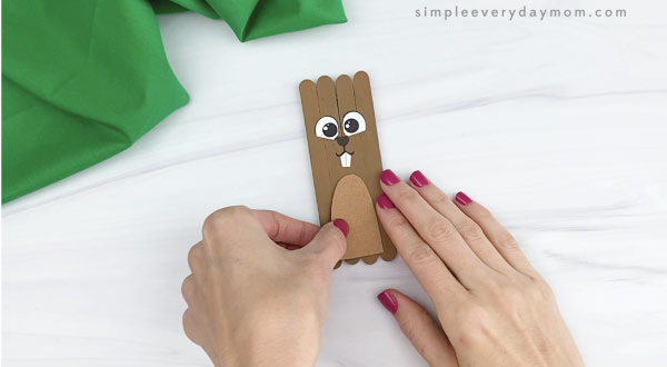 hand gluing belly onto popsicle stick groundhog craft